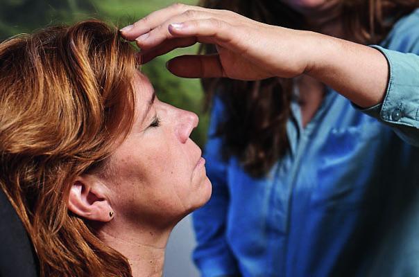 Hand liegt auf der Stirn einer Frau